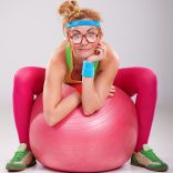 stock-photo-29118854-nerdy-fitness-girl-wearing-glasses-sitting-on-pink-pilates-ball_orig.jpg
